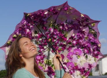 Fresh Dendrobium, Phalaenopsis and Vanda orchids on a pink flower umbrella