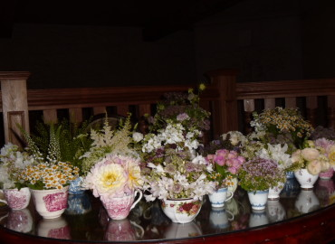 Teacups and cream jugs full of flowers